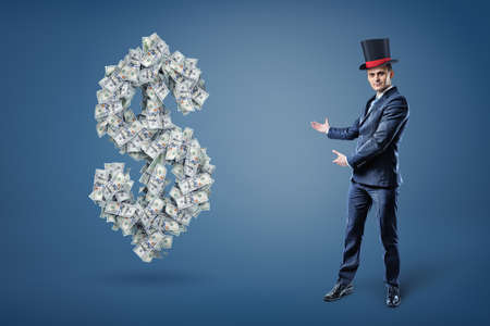 A businessman wearing a magicians hat and presents a large dollar sign made of many bills.