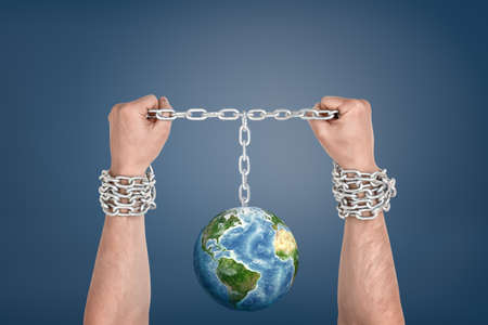 Two male hands bound together with chains and linked to an Earth globe between them.
