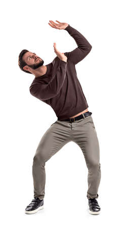 A bearded man in casual garb stands protecting himself with outstretched hands from something getting to him from above.