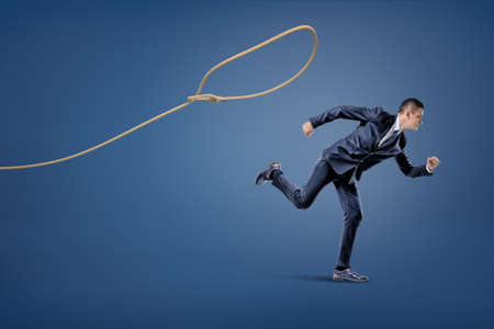 A businessman in a suit runs away from a rope lasso that tries to catch him. Foto de archivo