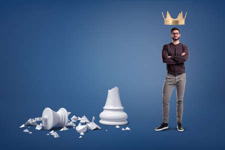 A bearded man stands with a large golden crown above his head and near a large broken chess figure.