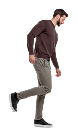 A serious looking man in casual clothes walks in a side view with one leg bent up behind him. Banco de Imagens
