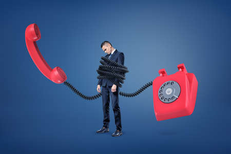 A small businessman stands bound by a huge plastic cord from a giant red retro phone. Stockfoto