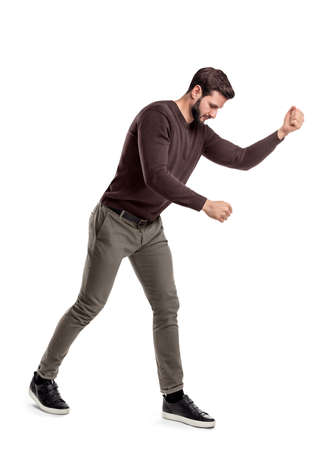 A fit bearded young man in casual clothes tries to hit or make something as if holding an invisible tool. Manual work. Hard labor. Difficult work.