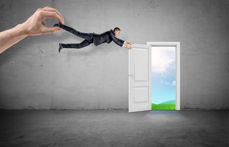 A businessman tries to hold an open door leaf leading to a valley but dragged away by a giant hand.