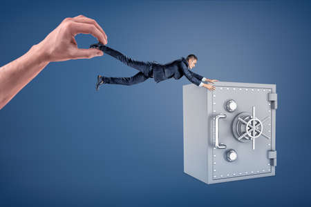 A giant hand holds a small businessman who fails to reach a large safe box. Stock fotó