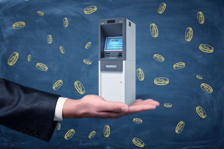A large businessmans hand holding a small ATM machine on a background with yellow dollar coins.