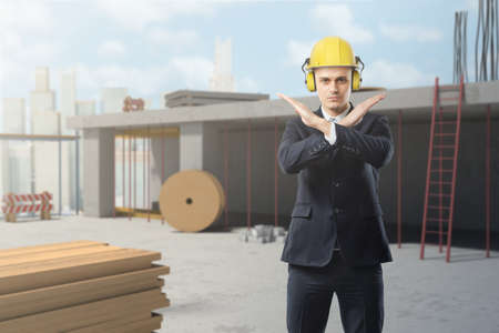 A businessman wears a yellow helmet on a construction site and makes a stop motion with his crossed arms. Stok Fotoğraf