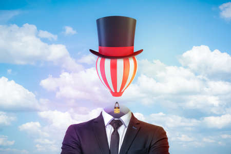Mannelijke figuur in slim pak, stropdas en tophat met een gestreepte luchtballon in plaats van het hoofd tegen blauwe lucht met witte wolken.