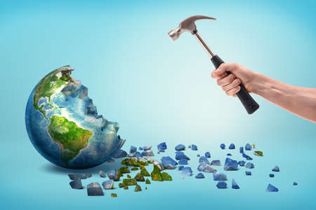 A male hand holds a metal hammer near a semi-broken Earth globe with small pieces fallen out of it.