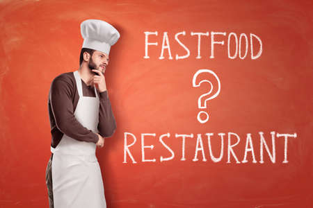 Chef with white apron and hat thinking over a sign FASTFOOD or RESTAURANT on red background Imagens - 114369587