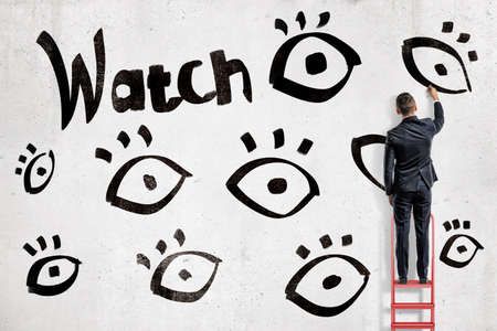 A businessman on a red stepladder draws black eye symbols near a word Watch on a white wall.