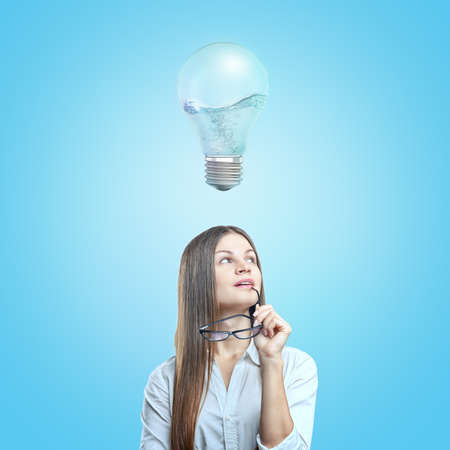 A young woman in a white shirt holding glasses in her hand with a 3d rendering of a bulb half-full with bubbling water. Imagens - 114370573