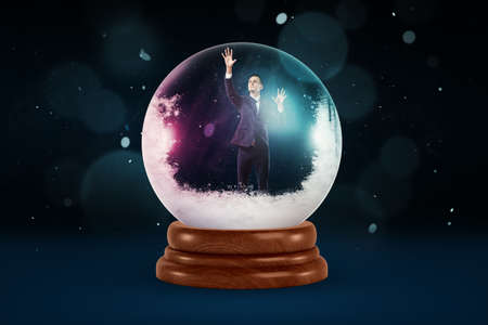 A tiny businessman inside a snowy crystal ball on a dark background with flecks of snow falling.