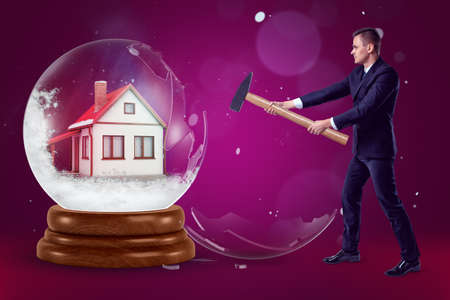 A businessman with a hammer in his hands crashing a crystal ball with a little house inside on a purple background with a few flecks of snow.