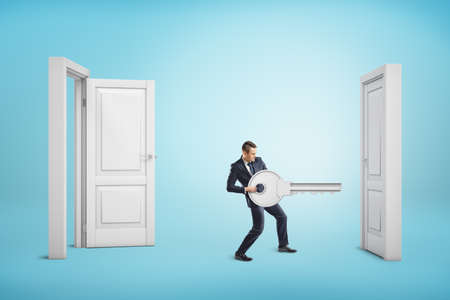Businessman holding big key between an open door and a closed one on blue background
