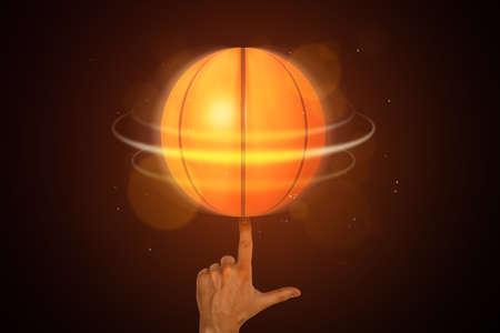 Neon orange basketball ball spinning on a finger on dark background