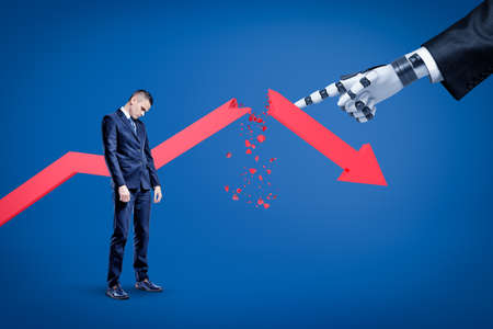 A sad businessman looking down with a broken red arrow behind and a big robotic hand in suit pointing at him. Imagens