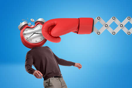 Huge red boxing glove punching man with an alarm clock instead of his face on blue background. 免版税图像