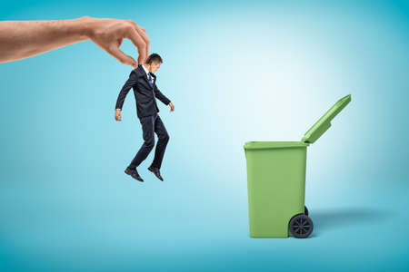 Big male hand throwing little businessman into green garbage bin on blue background Standard-Bild
