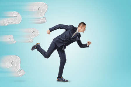 Businessman running from grey question marks on blue background