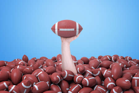 Male hand emerging from below a lot of balls for American football and holding one ball up.