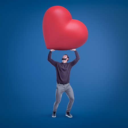 Young fit man in casual clothes holding up huge red Valentine heart on blue background. Stock fotó