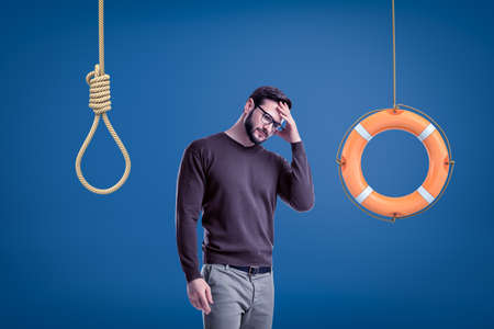 Man in casual outfit standing half-turn with hand on forehead as if choosing between lifebuoy hanging on rope and hangmans noose.