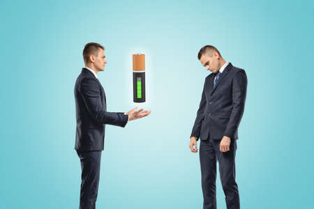 Two businessmen, one posing as if manually controlling the battery suspended in the air, the other standing half-turned with a sad expression on his face. Banque d'images