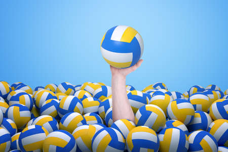 Male hand emerging from below a lot of volleyballs and holding one volleyball up. Stock Photo