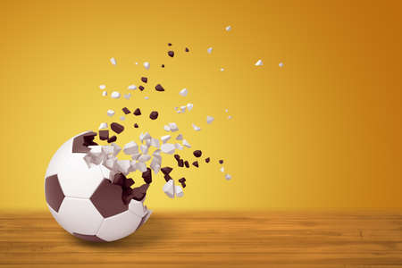 3d rendering of a football dissolving into particles on one side, on wooden surface on yellow background with much copy space. Stock Photo