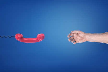 A red retro phone receiver hangs opposite to an empty male hand on a blue background.