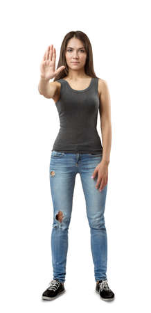 Young beautiful woman in gray sleeveless top and blue jeans standing and holding right hand out in stop gesture isolated on white background. 스톡 콘텐츠