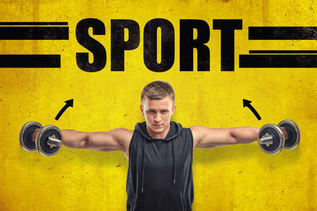 Close-up of young fit man in sleeveless hoody doing side lateral raise with dumbbells against yellow wall with title SPORT. Stock Photo