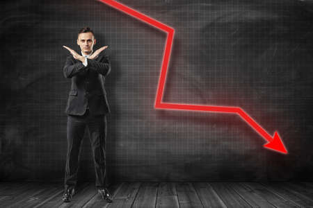 Businessman making rejection gesture with red arrow going down on black background