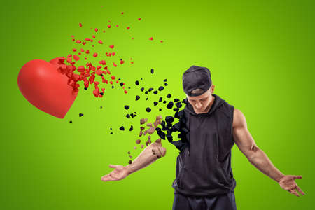 Young muscular man in black sport clothing and red heart shattering into small pieces on green background