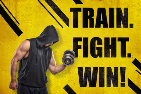 Strong muscular young man in black sportswear with a dumbbell and TRAIN. FIGHT. WIN  sign on yellow background Stockfoto