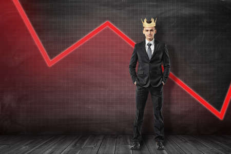 Businessman wearing golden crown with red diagram line on black background