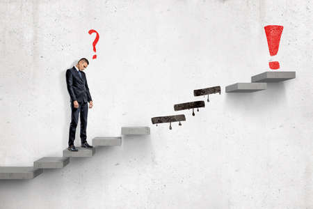 Sad businessman with red cartoon question mark standing on ladder to red exclamation mark with several steps missing on white wall background Stock Photo