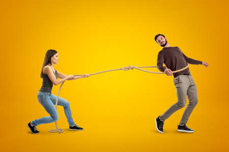Side view of young woman lassooing young man on yellow background. Stock Photo