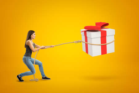 Side view of young woman standing with bent knees and pulling big gift box in air which she has lassoed, on yellow background.