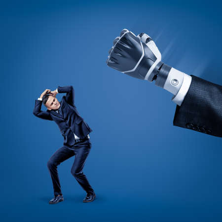 Businessman covering his head with hands to protect himself from big robot hand in suit. Stock Photo