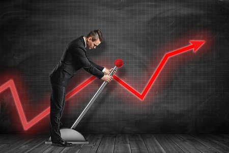 Vista lateral del empresario mirando hacia abajo y tirando de la palanca grande cerca de la pared gobernada por el gráfico negro con la flecha roja del gráfico.