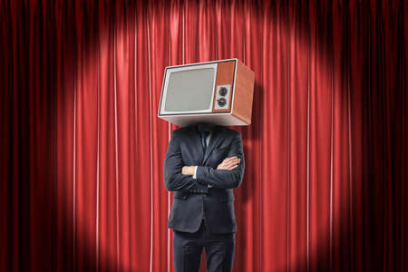 Man in suit standing with arms folded, with TV set instead head, in spotlight near red stage curtain.
