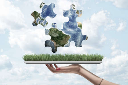 Female hand holding a grass model and earth globe puzzle pieces above on blue sky background
