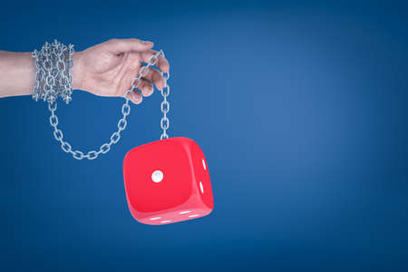 Male hand chained to red dice on blue background