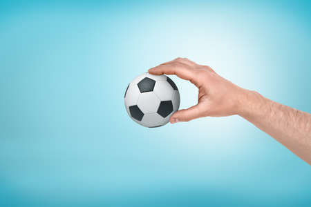 Male hand holding small football ball between fingers on blue background