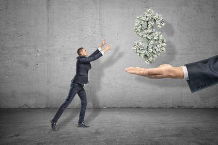 Seitenansicht eines miniaturisierten Geschäftsmannes, der die Hände ausstreckt, um das Dollarsymbol zu greifen, das aus vielen Banknoten besteht, die in der Luft über der Hand des großen Mannes hängen.