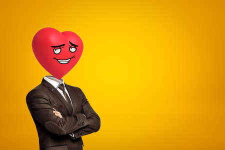 Businessman with red cartoon smiley heart instead of head on yellow background