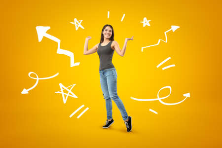 Young happy brunette girl wearing casual jeans and t-shirt with cartoon arrows, lines and stars on yellow background